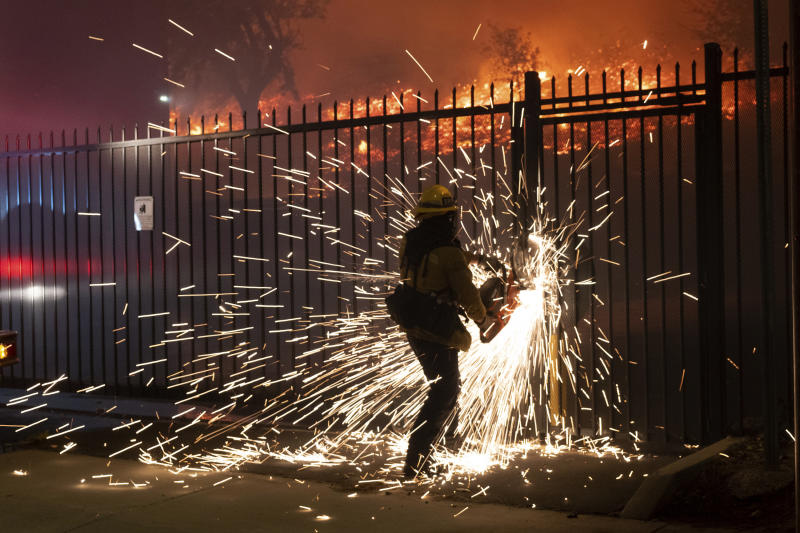 A firefighter cuts though a fence to gain access to the Saddleridge fire along Yarnell Street in Sylmar, Calif., Friday, Oct. 11, 2019. (David Crane/The Orange County Register via AP)