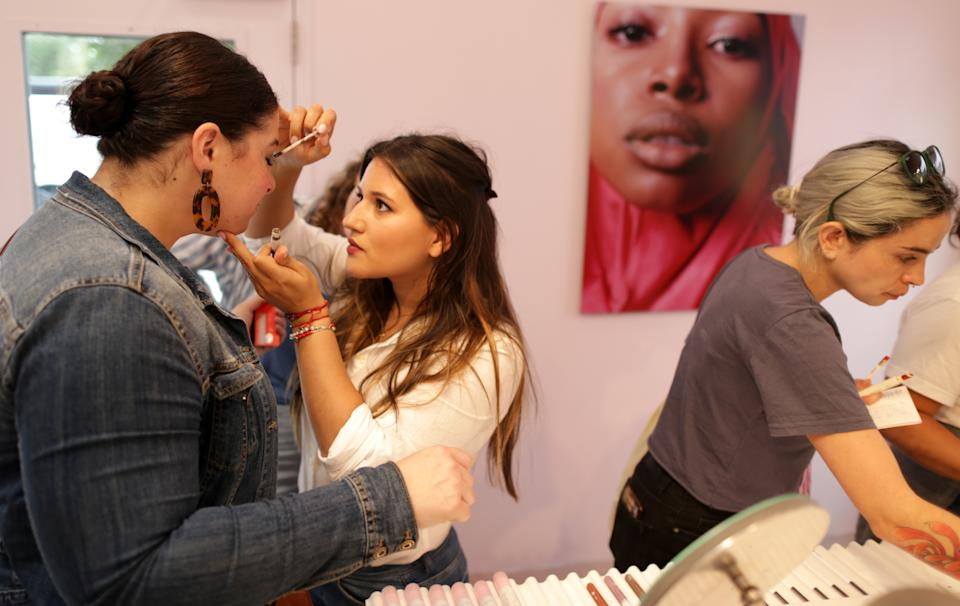 BOSTON, MA - AUGUST 7: Sheree Dunwell, left, gets some help from makeup artist Iris Henriquez at the Glossier pop-up in Boston's Seaport District on Aug. 7, 2019. Glossier is a billion-dollar Instagram-driven makeup brand with a pop-up in the Seaport through October 4. (Photo by Jonathan Wiggs/The Boston Globe via Getty Images)