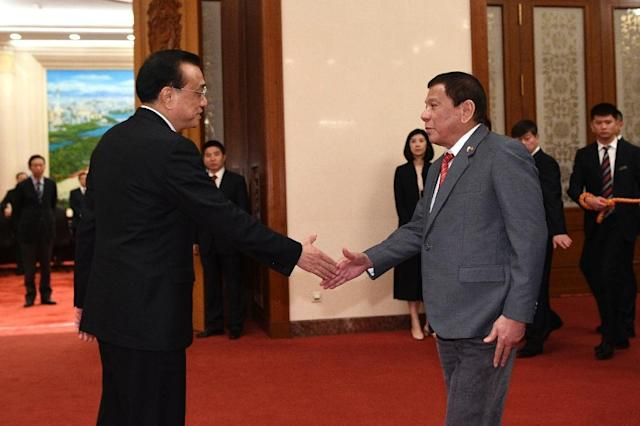 Chinese Premier Li Keqiang (L) shakes hands with Philippine President Rodrigo Duterte before a meeting at the Great Hall of the People in Beijing (AFP Photo/Parker Song)