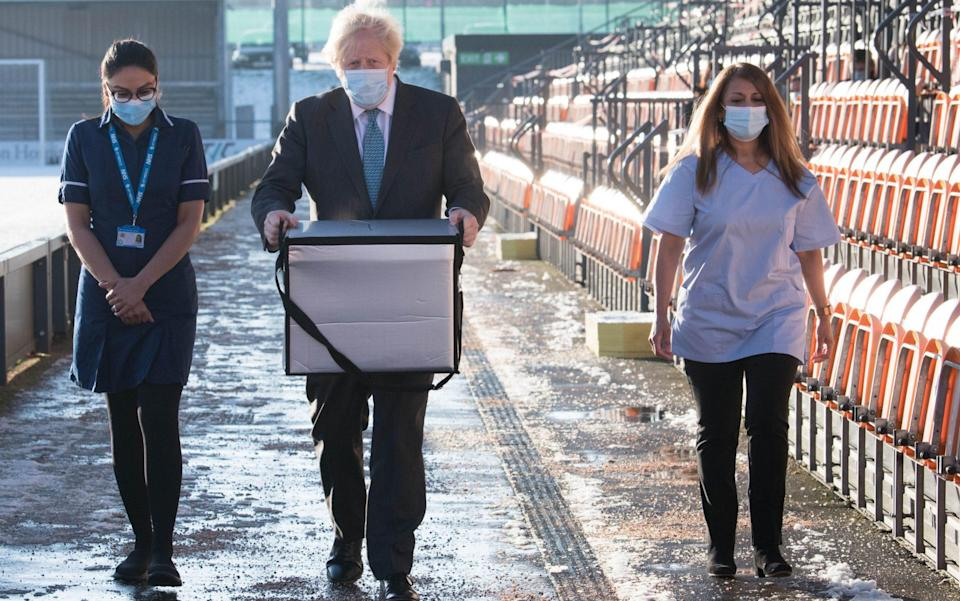 Boris Johnson carries doses of the Oxford/AstraZeneca coronavirus vaccine for mobile distribution at Barnet FC's ground in north London - Getty Images Europe