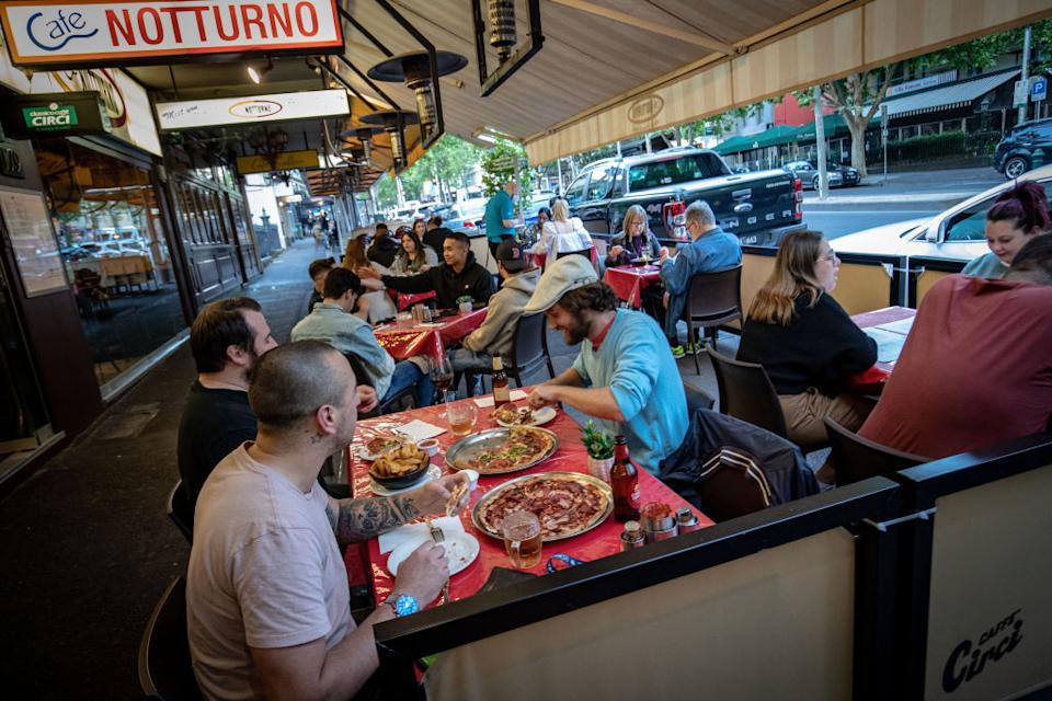 Groups of people dining outdoors on Lygon Street, Carlton.