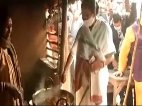Chief Minister Mamata Banerjee helping a tribal woman cook at a small hotel in  Ballavpur Danga Village