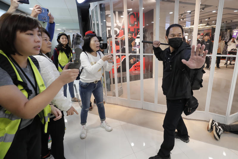 "An undercover policeman holds a baton during a demonstration at a shopping mall popular with traders from mainland China near the Chinese border in Hong Kong, Saturday, Dec. 28, 2019. Protesters shouting ""Liberate Hong Kong!"" marched through a shopping mall Saturday to demand that mainland Chinese traders leave the territory in a fresh weekend of anti-government tension. (AP Photo/Lee Jin-man)"