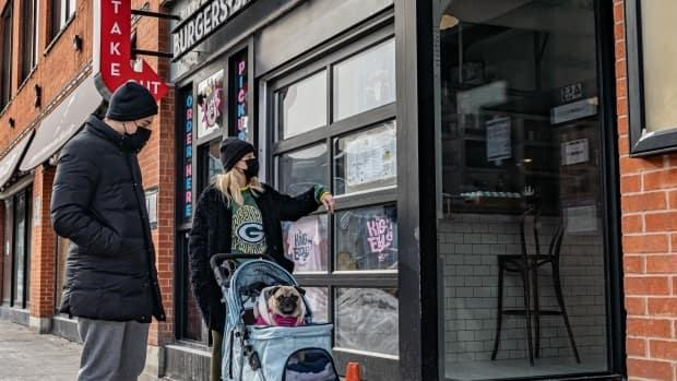 A couple pushing a pug in a stroller checks out the menu of a restaurant in downtown Ottawa. Scientists warn the city's COVID-19 numbers could easily increase if people aren't careful, especially with new variants making their way across the province.