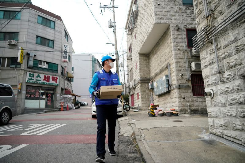 A delivery man for Coupang Jung Im-hong wearing a mask to prevent contracting the coronavirus, checks an address as he works in Incheon