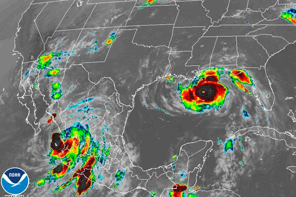 This image provided by the National Oceanic and Atmospheric Administration (NOAA) shows severe weather systems, Hurricane Nora, lower left, and Hurricane Ida, right, over the North American continent (AP)