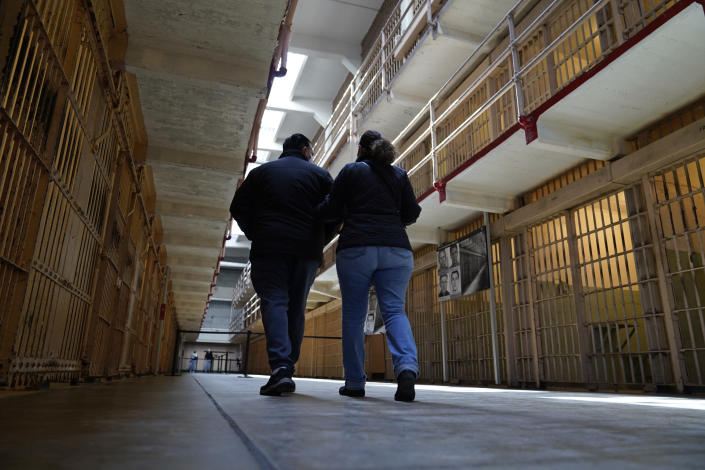 A couple walks through the main cell house on Alcatraz Island in San Francisco, Monday, March 15, 2021. The historic island prison was reopened to visitors Monday after being closed since December because of the coronavirus threat. Visitors were also able to tour the inside of the main cell house for the first time in a year. (AP Photo/Eric Risberg)