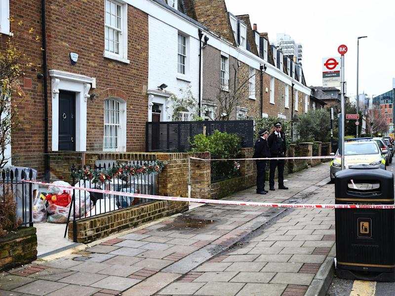 Police stand outside the crime scene where Flamur Beqiri, 36, a father of one, was murdered on Christmas Eve: Getty Images