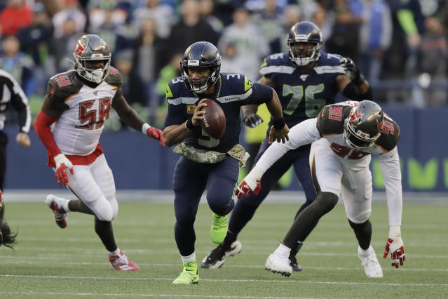 Seattle Seahawks quarterback Russell Wilson (3) scrambles away from Tampa Bay Buccaneers defensive end Jason Pierre-Paul (90) during overtime of an NFL football game, Sunday, Nov. 3, 2019, in Seattle. (AP Photo/John Froschauer)