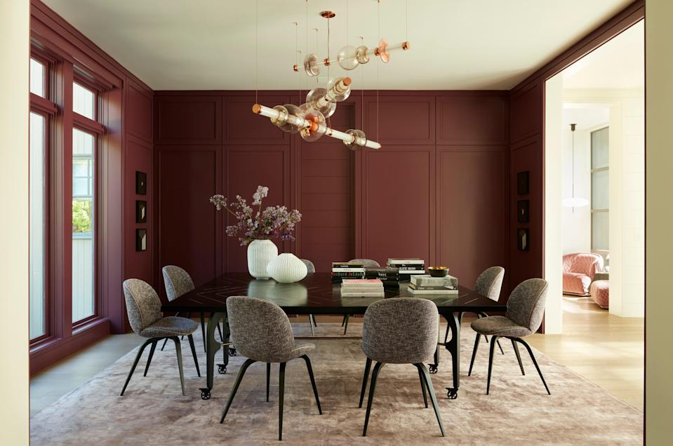 """The dining room walls weren't initially painted purple, but something inspired Lau to take the bold plunge. """"Edel knew what she was talking about,"""" says Lau, who adds, """"I'm excited to start entertaining inside again."""" The Kelly Lamb God's Eye Table is surrounded by Gubi Beetle chairs upholstered in Knoll fabric and Holly Hunt leather trim detail. Hanging from the ceiling is a Gabriel Scott Luna Three Tier Chandelier that shines against the aubergine wall color, which is Wine Stain by Dunn Edwards."""