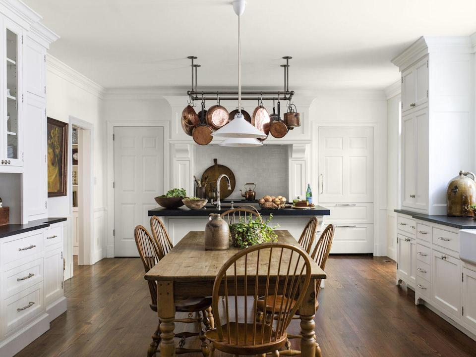 <p>Materials and accessories with a throwback to Colonial-era interiors (soapstone countertops, a scrub pine farm table, stoneware jugs) feel right at home in this light and bright setting. A ceiling-mount pot rack displays the homeowner's horde of French copper cookware that warms up this white kitchen.</p>