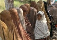 Women wait their turn to receive cash vouchers from an officer under the government's Ehsaas Emergency Cash program for families in need, in Peshawar, Pakistan, Tuesday, June 1, 2021. (AP Photo/Muhammad Sajjad)