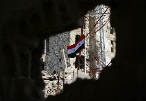 The Syrian national flag flies among damaged buildings in an opposition-held part of the southern city of Daraa on July 12, 2018