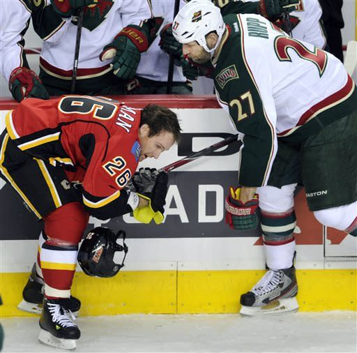 Calgary Flames' Dennis Wideman, left, loses his helmet after getting tangled with Minnesota Wild's Mike Rupp during the second period of an NHL hockey game in Calgary, Alberta, Monday, April 15, 2013. (AP Photo/The Canadian Press, Larry MacDougal)