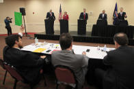 A moderator signals 30-seconds remaining to senate candidate Rep. Roger Marshall, R-Kan., right, during a GOP senatorial debate In Manhattan, Kan., Saturday, May 23, 2020. David Lindstrom, left, Susan Wagle, second from left, Kris Kobach, middle, and Bob Hamilton, second from right, share the debate stage. (AP Photo/Orlin Wagner)