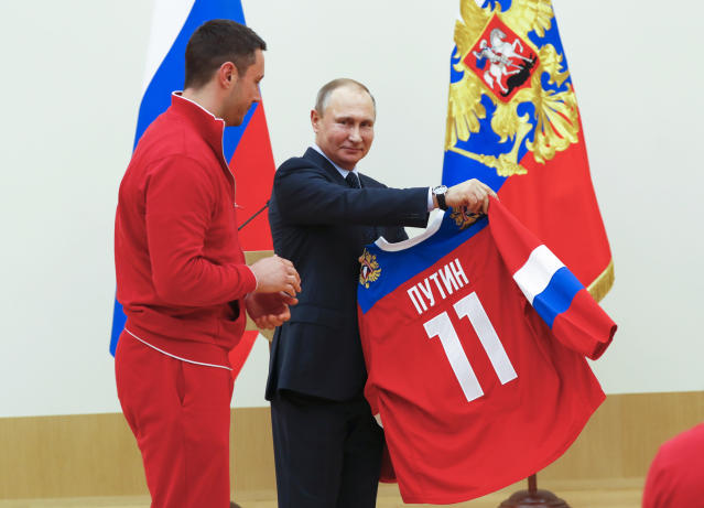 Russian President Vladimir Putin, receives a jersey from ice hockey player Ilya Kovalchuk, left, during a meeting with the Russian athletes who will take part in the upcoming 2018 Winter Olympic Games. (Grigory Dukor/Pool Photo via AP)