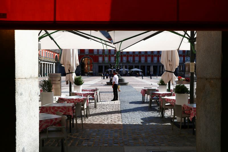 FILE PHOTO: A waiter wearing a protective face mask waits for customers in his terrace at Plaza Mayor square amid the outbreak of the coronavirus disease (COVID-19) in Madrid