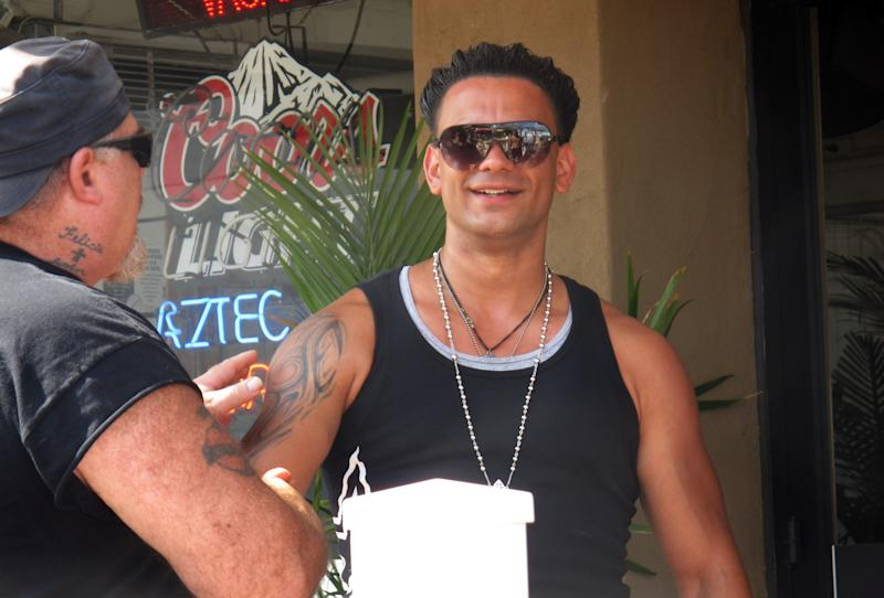 """In this July 3, 2012 photo, a bar customer, at left, mistakes Michael Maldonado, of New York, right, for Paul """"Pauly D"""" DelVecchio of the MTV series """"Jersey Shore,"""" at a bar in Seaside Heights, N.J. Maldonado bears a strong resemblance to the reality TV star. (AP Photo/Wayne Parry)"""