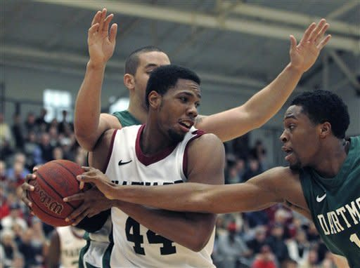 Harvard forward Keith Wright (44) is surrounded by Dartmouth guard R.J. Griffin, right, and forward Gabas Maldunas, rear, as he looks to pass in the first half during an NCAA college basketball game in Cambridge, Mass., Saturday Jan. 7, 2012. (AP Photo/Charles Krupa)
