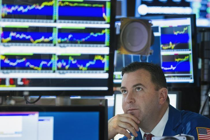 A trader looks up at screen as he works on floor of New York Stock Exchange shortly before closing of the market in New York