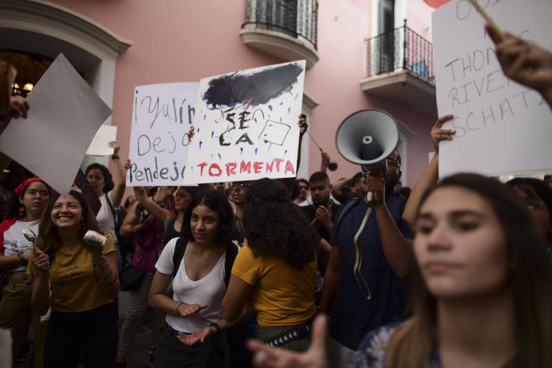 "A young man holds a sign that reads in Spanish ""Be the storm"" while protesting outside the executive mansion known has La Fortaleza, in Old San Juan, demanding the resignation of Governor Wanda Vazquez after the discovery of an old warehouse filled with unused emergency supplies in San Juan, Puerto Rico, Monday, Jan. 20, 2020. Anger erupted on Saturday after an online blogger posted a live video of the warehouse in the southern coastal city of Ponce filled with water bottles, cots, baby food and other basic supplies that had apparently been sitting there since Hurricane Maria battered the U.S. territory in September 2017. (AP Photo/Carlos Giusti)"
