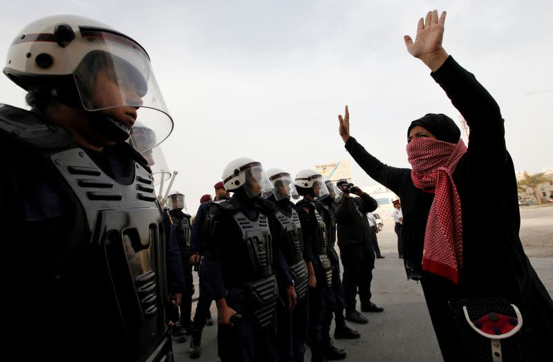 FILE PHOTO: An anti-government protester faces off with riot police during a march to Al Farook Junction
