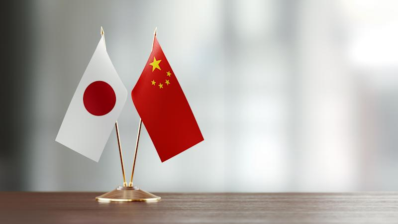 Japanese and Chinese flag pair on desk over defocused background. Horizontal composition with copy space and selective focus.