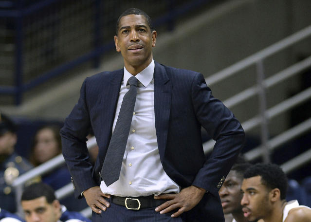 FILE - In this Feb. 7, 2018, file photo, Connecticut head coach Kevin Ollie watches from the sideline during the first half an NCAA college basketball game in Storrs, Conn. The arbitrator in the dispute between UConn and Kevin Ollie has ruled that the former basketball coach is protected by a union contract when it comes to the standard the school must meet in proving his firing was justified. UConn had argued that Ollie's personal contract superseded the union deal, allowing it to fire him in March, 2018 for a broader range of offenses. (AP Photo/Jessica Hill, File)