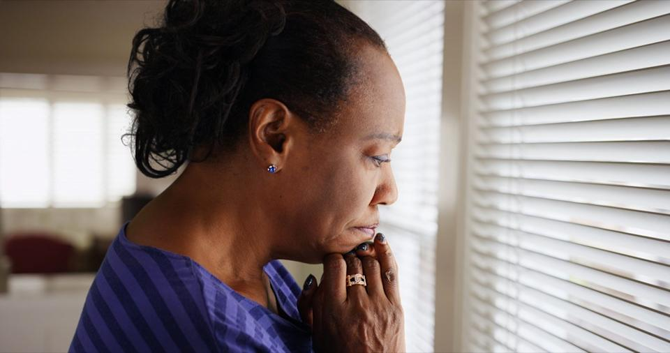 older black woman looking out window looking sad