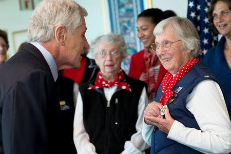 Phyllis Gould (R) shows Secretary of Defense Chuck Hagel a badge that she wore while working during World War II, during a visit at the Pentagon, in Arlington, Virginia, U.S., March 31, 2014. Erin A. Kirk-Cuomo/DOD/Handout via REUTERS