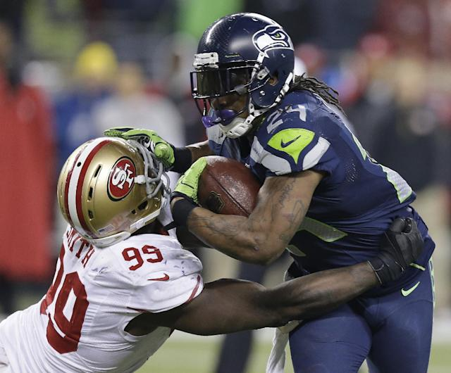 Seattle Seahawks' Marshawn Lynch tries to run past San Francisco 49ers' Aldon Smith during the second half of the NFL football NFC Championship game Sunday, Jan. 19, 2014, in Seattle. (AP Photo/Elaine Thompson)