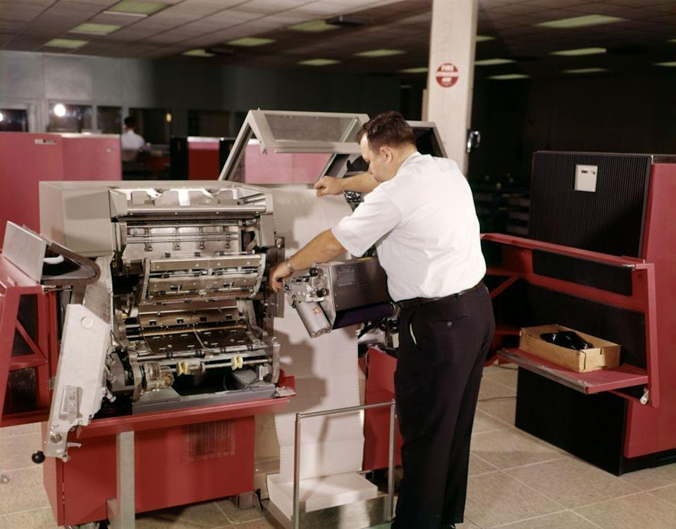 <p>A technician works with a computer printer and the big rolls of paper these machines required. Moving into the 1970's, dot-matrix printers and line printers were the most common types for general use, and many innovations of that time led to the modern day printers we use today. </p>
