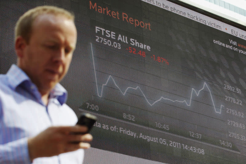 FILE PHOTO: A man passes a screen showing the activity of the FTSE index at Canary Wharf financial district in London August 5, 2011. REUTERS/Luke MacGregor/File Photo