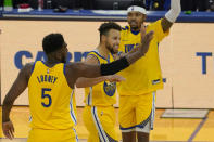 Golden State Warriors guard Stephen Curry, center, is congratulated by forwards Kevon Looney (5) and Kent Bazemore after scoring against the Sacramento Kings during the first half of an NBA basketball game in San Francisco, Monday, Jan. 4, 2021. (AP Photo/Jeff Chiu)