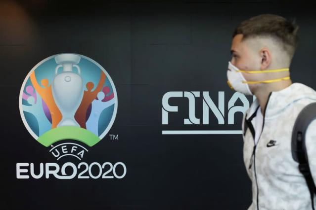 Travellers pass by a logo of the 2020 UEFA European Football Championship displayed on a wall inside Bucharest Henri Coanda International Airport