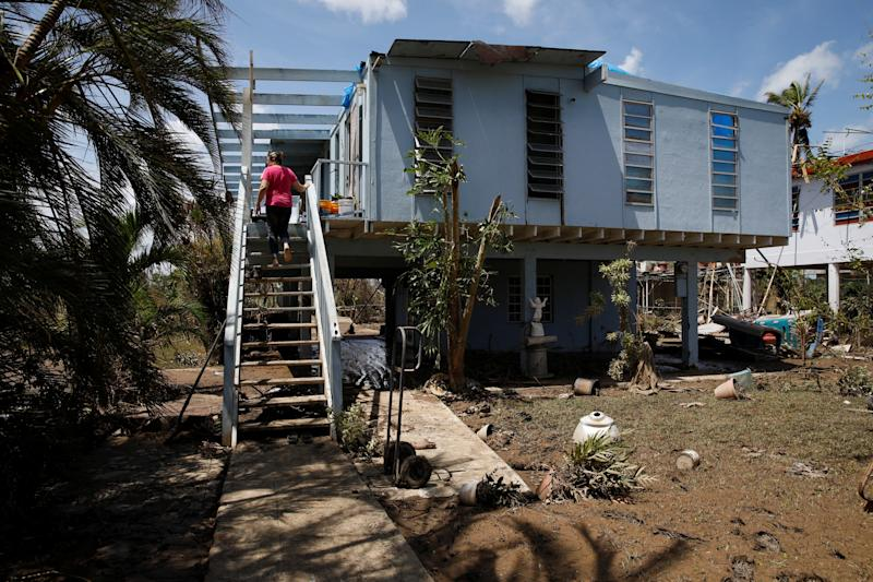 A woman looks at the damages to her house after the area was hit by Hurricane Maria in Toa Baja, Puerto Rico