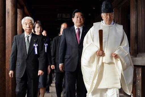 <p>Japanese lawmakers follow a Shinto priest during a visit to the controversial Yasukuni shrine in Tokyo on October 18, 2013</p>