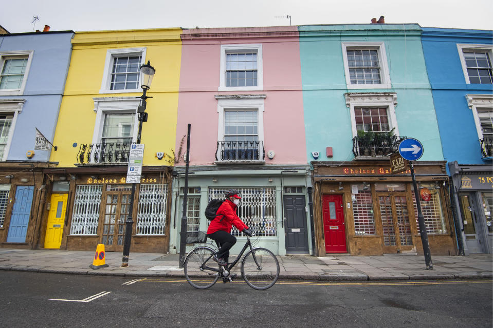 A cyclist wearing a face mask rides past closed up shops on Portobello Road in West London as the UK continues in lockdown to help curb the spread of the coronavirus. (Photo by Victoria Jones/PA Images via Getty Images)