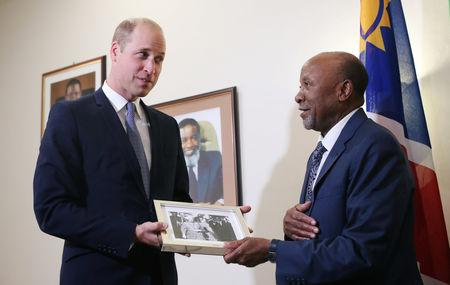 Britain's Prince William presents a gift to Namibia's Vice President Nangolo Mbumba during their meeting in Windhoek, Namibia September 24, 2018.    REUTERS/Mike Hutchings