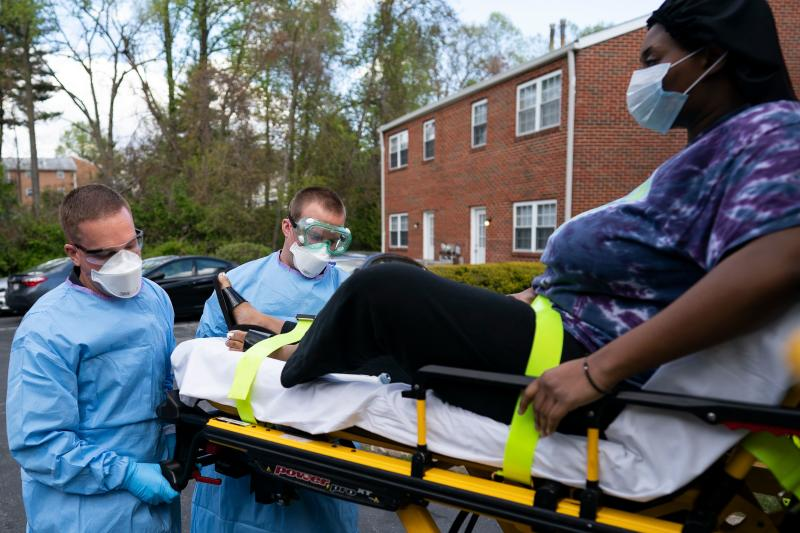 Paramedics and firefighters with Anne Arundel County Fire Department load a confirmed COVID-19 patient onto the ambulance on April 21, 2020 in Glen Burnie, Maryland. (Photo by Alex Edelman / AFP) / RESTRICTED TO EDITORIAL USE (Photo by ALEX EDELMAN/AFP via Getty Images)