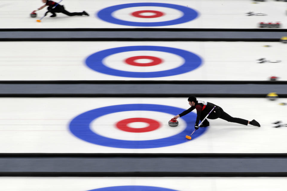 """Local team players compete in a curling competition during a test event for the 2022 Beijing Winter Olympics at National Aquatic Center, also known as the """"Water Cube"""" in Beijing, Thursday, April 1, 2021. Chinese capital hold a 10 days test events for 2022 Beijing Winter Olympics in five different venues from April 1-10, becomes the first city to hold both the Winter and Summer Olympics. (AP Photo/Andy Wong)"""