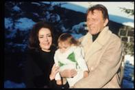 """<p>Elizabeth is photographed in Gstaad, Switzerland with her husband Richard and her <a href=""""https://www.thelist.com/128553/elizabeth-taylors-grandchildren-grew-up-to-be-gorgeous/"""" rel=""""nofollow noopener"""" target=""""_blank"""" data-ylk=""""slk:first grandchild"""" class=""""link rapid-noclick-resp"""">first grandchild</a>, Laela Wilding. </p>"""