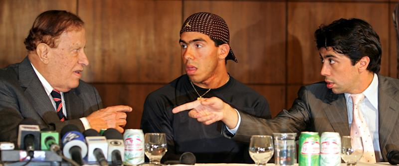 Argentine and former Boca Juniors soccer player Carlos Tevez, center, looks as Corinthians President Alberto Dualib, left, talks to Kia Joorabichian, right, of the London-based group Media Sports Investments during the presentation of Tevez in the Brazilian team in Sao Paulo, Thursday, Jan. 13, 2005. (AP Photo/Victor R. Caivano) **EFE OUT**