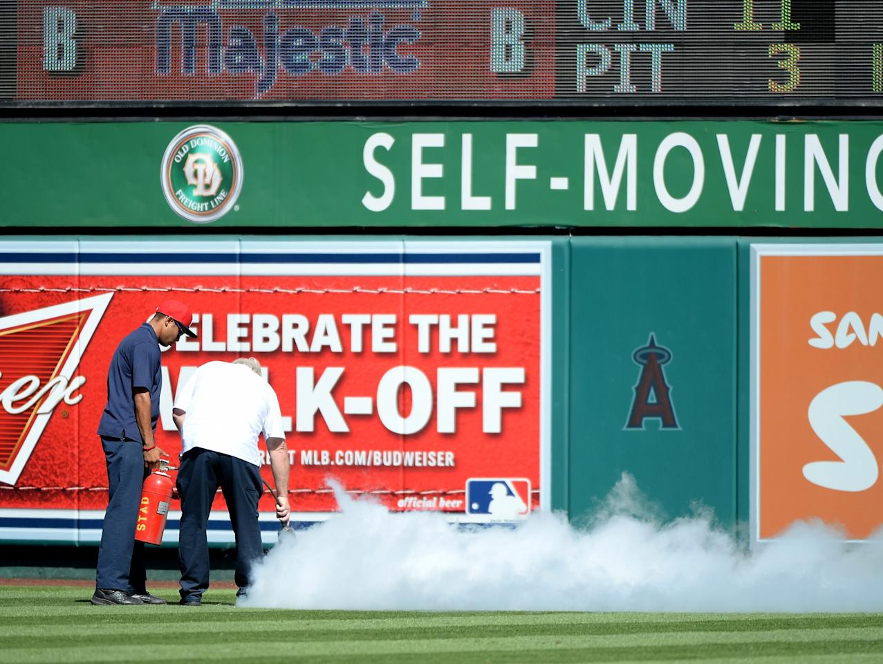 ANAHEIM, CA - SEPTEMBER 22: Groundscrew attempt to remove bees in centerfield which delayed the game between the Seattle Mariners and the Los Angeles Angels during the fourth inning at Angel Stadium of Anaheim on September 22, 2013 in Anaheim, California. (Photo by Harry How/Getty Images)