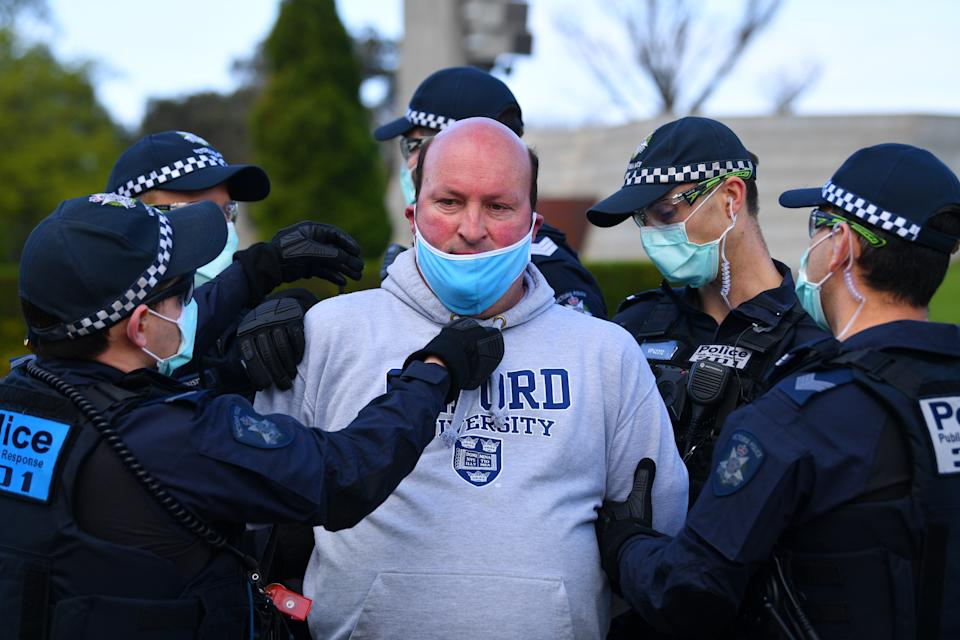 Victoria Police arrest and put a face mask on a protester outside on Saturday. Source: AAP
