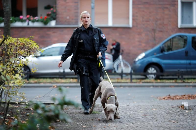 A police officer is seen with a police dog outside the house of a Syrian man suspected of exchanging bomb building material that was arrested earlier today in Berlin