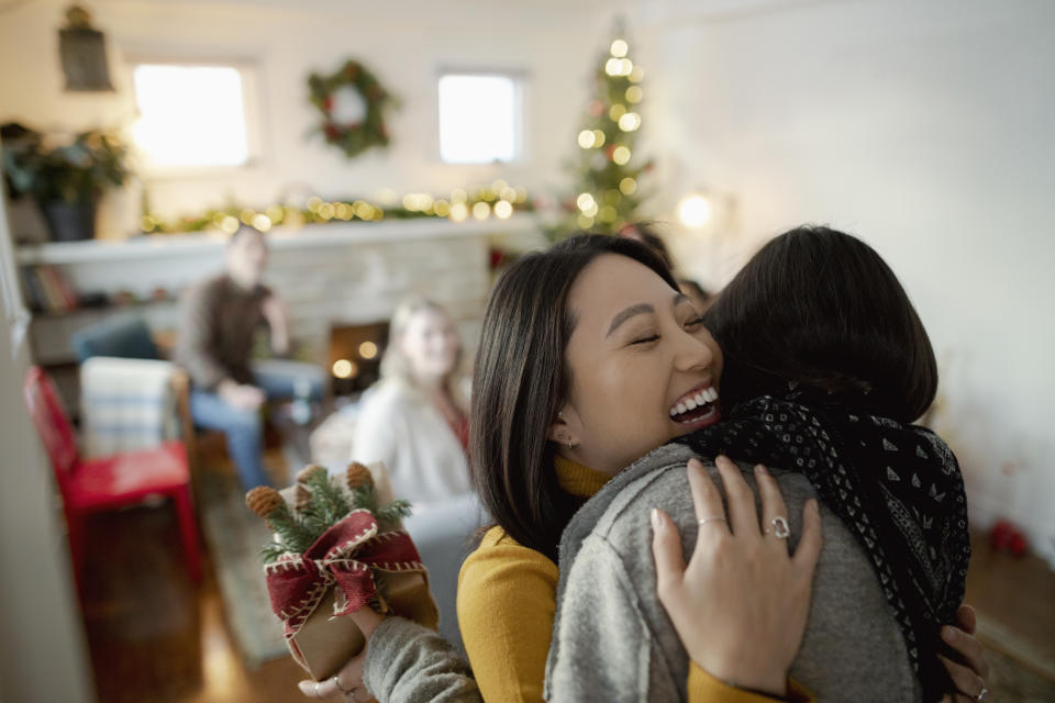 Happy young woman greeting friend with Christmas gift