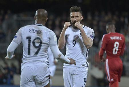 France's Olivier Giroud celebrates scoring their first goal with Djibril Sidibe