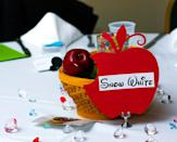 photo by:Shari Photography<br> The guest tables were outfitted in different Disney-themes. The Snow White table included a poisonous apple centerpiece.