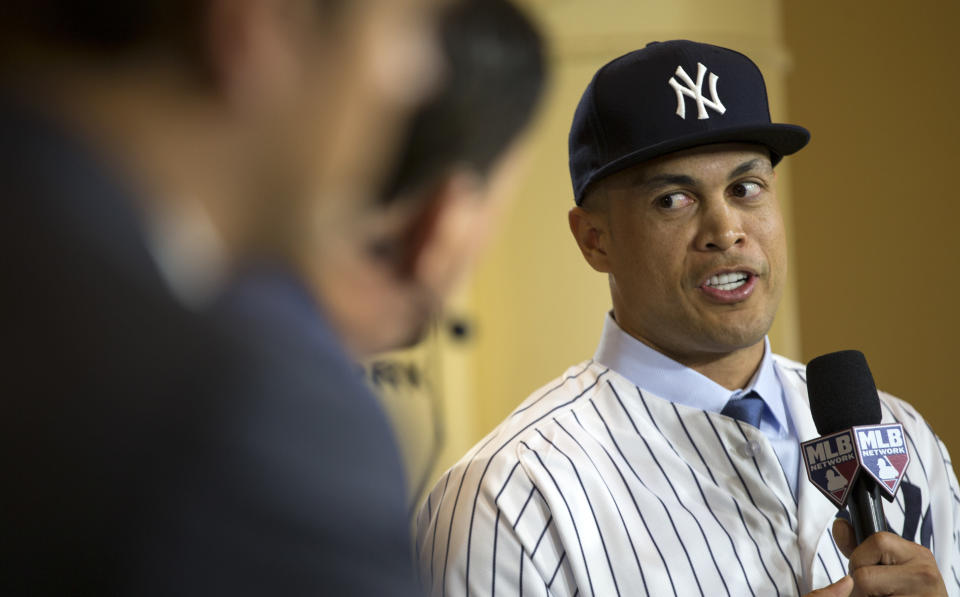 New Yankee Giancarlo Stanton talks with reporters on set during the Major League Baseball winter meetings in Orlando, Fla., Monday, Dec. 11, 2017. (AP)